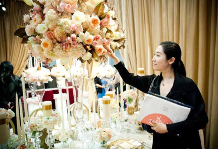 Image of professional planner inspecting the details of a flower arrangement.