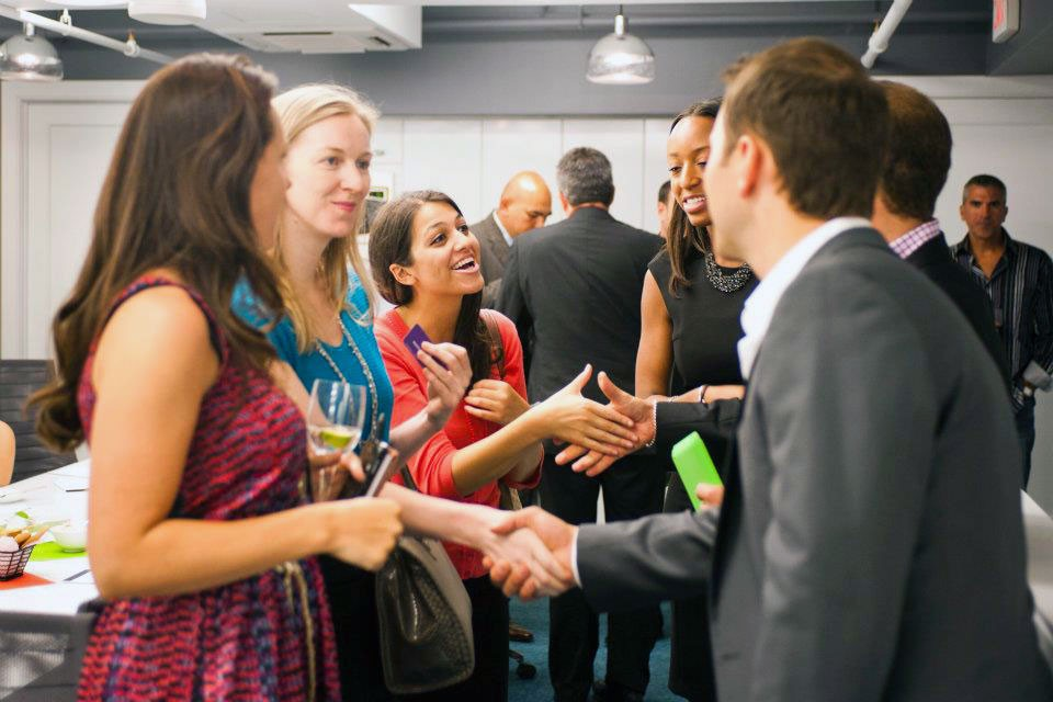 Image of several professionals meeting at an event shaking hands and networking.